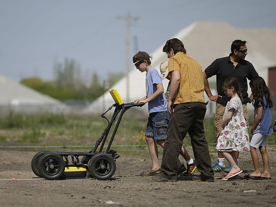 Aspen Holterman, 12, of Green Bay, uses a ground penetrating radar during an archaeological survey of the old Fort Howard military site in downtown Green Bay.