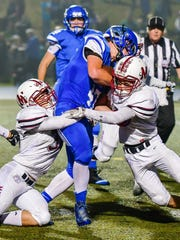 Lakeland's Dakota Myers (middle) is sandwiched by two