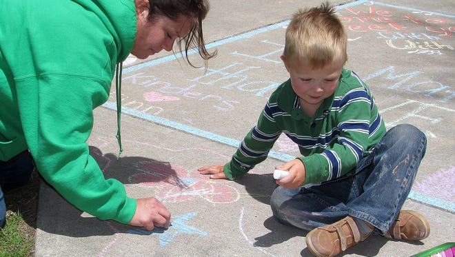 Christi Bond and her son Benji, 4, decorate the sidewalk outside Finn Academy in Elmira with chalk on Monday.