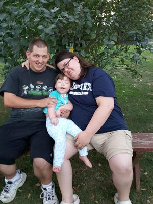 Celena Keeney sitting with her parents, Chris and Kara Keeney, of Richland.