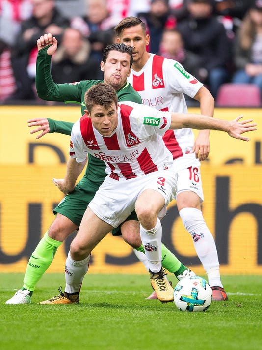 Cologne's  Dominique Heintz, front, and Bremen's Zlatko Junuzovic, center, and Cologne's Pawel Olkowski challenge for the ball during the German Bundesliga soccer match between 1. FC Cologne and SV Weder Bremen in Cologne, Germany, Sunday, Oct. 22, 2017. (Marius Becker/dpa via AP)