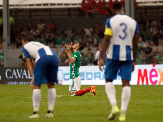 Mexico's Luis Reyes kneels and prays at the end of a 2018 Russia World Cup qualifying soccer match between Mexico and Honduras at Azteca Stadium in Mexico City, Thursday, June 8, 2017. Mexico won the match 3-0. (AP Photo/Eduardo Verdugo)