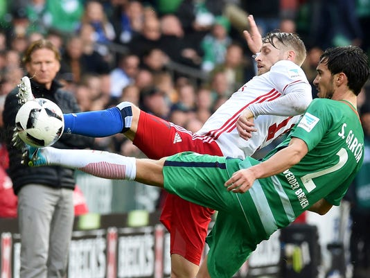 Bremen's Santiago Garcia, right, and Hamburg's  Aaron Hunt challenge for the ball during the German Bundesliga soccer match between SV Werder Bremen and Hamburger SV, in Bremen, northern Germany, Sunday, April 16, 2017. (Carmen Jaspersen/dpa via AP)
