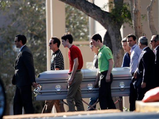 Pall bearers carry the casket of Scott Beigel after