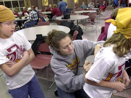 Roosevelt High School basketball player Lindsay Thomas signs the back of Arika Olson's t-shirt (right) as her friend Abbey Fujan watches and waits for an autograph for her t-shirt during the girls basketball homecoming celebration Sunday at the school.
