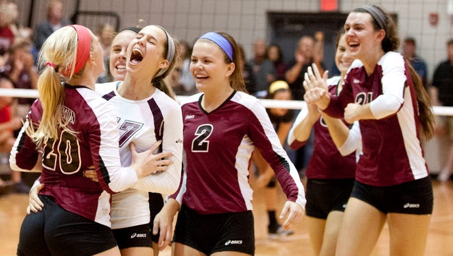 Assumption teammates including Cassidy Anderson, left, Molly Sauer, second from left, and McKenzie Watson, center, celebrate their victory over Mercy defeating their rivlas, 3-1. Oct. 10, 2013