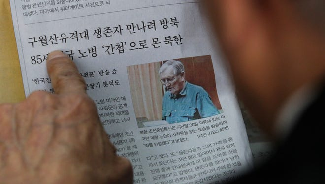 A former member of the Kuwol partisan unit, reads a newspaper reporting on Merrill Newman, an elderly American tourist detained in North Korea.