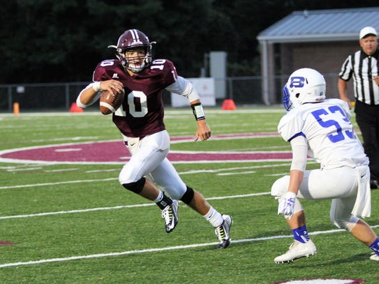 Junior varsity quarterback Caleb Scott scrambles to