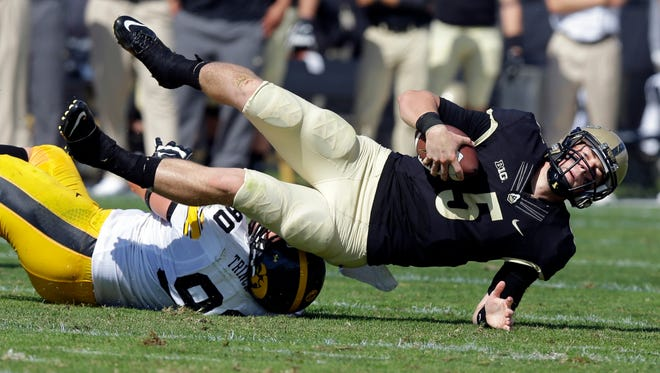 Iowa defensive lineman Louis Trinca-Pasat, left, sacks Purdue quarterback Danny Etling during the first half of an NCAA college football game in West Lafayette, Ind., Saturday, Sept. 27, 2014. (AP Photo/Michael Conroy)