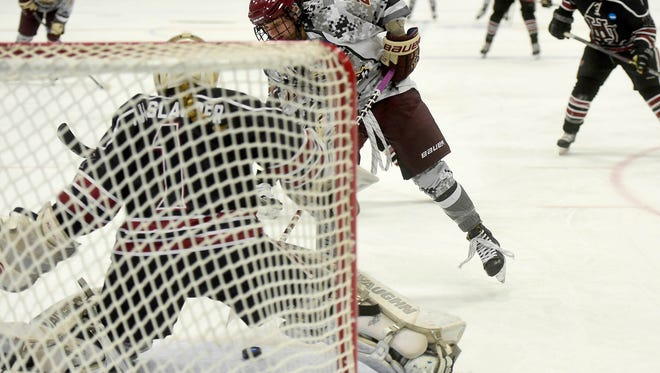 Norwich University junior Robyn Foley slips the puck between the pads of Hamline University freshman goalie McKenna Hulslander during the first period of their NCAA semifinal game Friday.