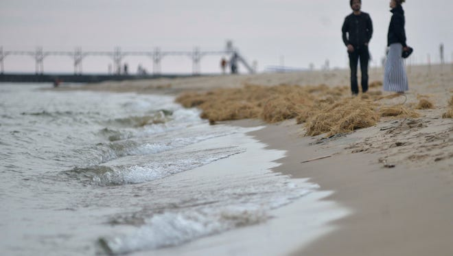 People enjoy the beach at Grand Haven State Park May 20th, 2016.  Erosion and near-record-high lake levels have reduced what had been expansive stretches of beach around the West Michigan shoreline.  It has currently risen 4 feet since January 2013, when it hit a record low. It's in contrast to water levels for Lake Michigan and Lake Huron in 2013, which were 2 feet below average.  (Photo By | Katy Batdorff)