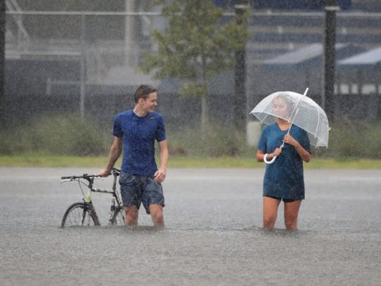 HOUSTON, TX - AUGUST 27: Cade Ritter (L) and Mari Zertuche walk through a flooded parking lot on the campus of Rice University afer it was inundated with water from Hurricane Harvey on August 27, 2017 in Houston, Texas. Harvey, which made landfall north of Corpus Christi late Friday evening, is expected to dump upwards to 40 inches of rain in areas of Texas over the next couple of days. (Photo by Scott Olson/Getty Images)