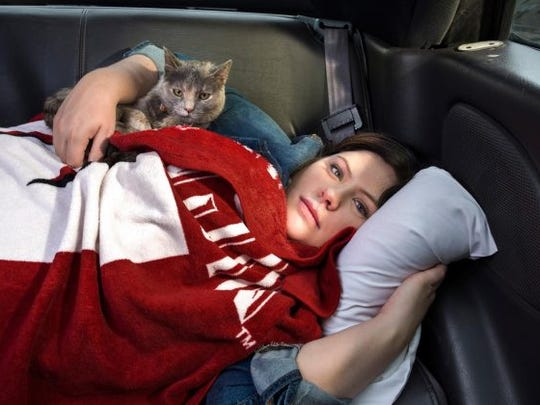 Brooke Evans, a homeless college student, with her cat, Kiki, in the car she called home for many months.