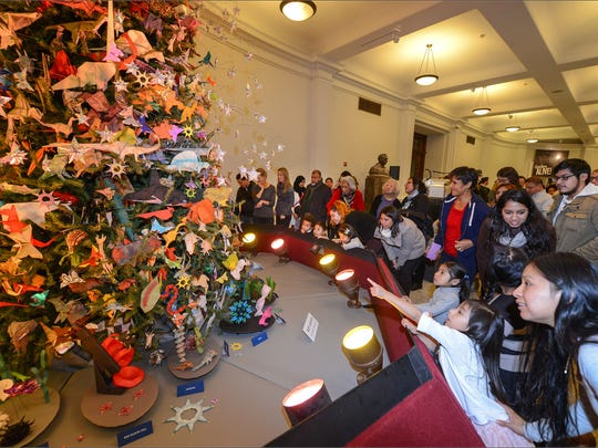 Visitors view the 2015 Christmas tree at the American Museum of Natural History.