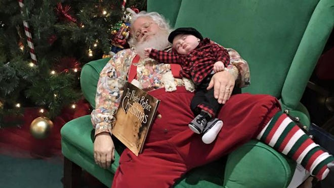 In this Nov. 25, 2015 photo provided by Donnie Walters, Walters' son Zeke snuggles up on Santa's lap during a visit to a shopping mall in Evansville, Ind.  Walters said his son fell asleep waiting in line and when they go to Santa, he asked him not to wake the boy. Santa leaned back in the big green chair with Zeke and a copy of The Night Before Christmas posing for a photo that makes it look like the pair fell asleep.
