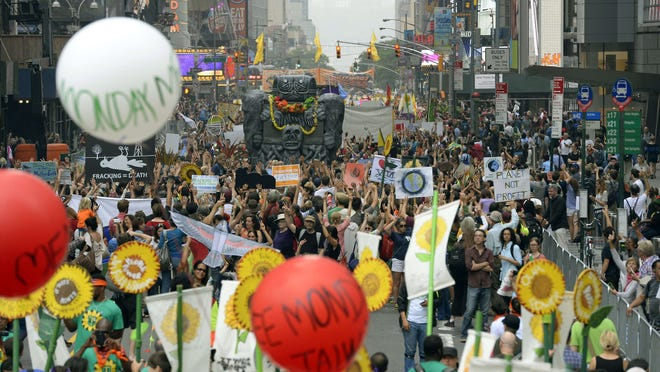 Marchers come down New York's 6th Avenue on Sunday during the People's Climate March