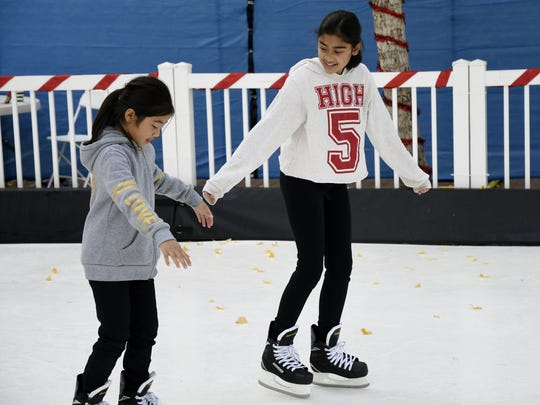Neveah See, 11, teaches sister Kaori See-Saelee, 8, how to skate at Ice Skate Visalia on Saturday afternoon.