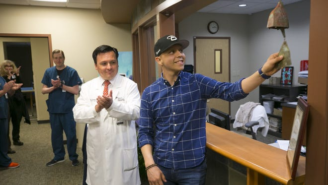 Jorge Rivera, 18, of Phoenix, rings a celebratory bell following his final treatment of radiation therapy for his Ewing's sarcoma, a rare type of bone cancer at Banner Desert Medical Center in Mesa on Feb. 6, 2018. Jorge's radiation oncologist, Dr. Yerko Borghero, looks on and applauds.