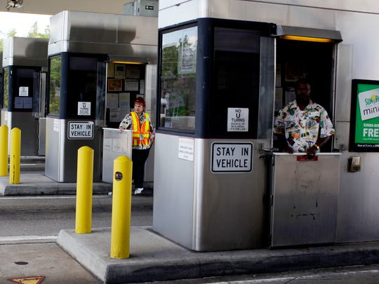 Toll collectors work at the booths entering Alligator Alley in Naples on Feb. 16, 2011.