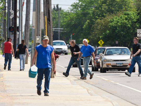 Employees leave Electrolux and cross 33rd Avenue North