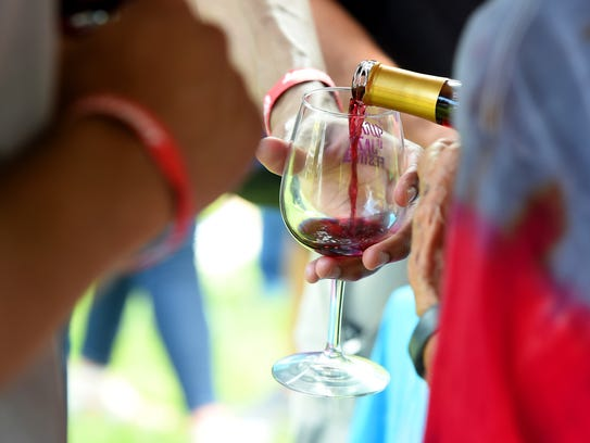 A sample of wine is poured into the glass of a festival