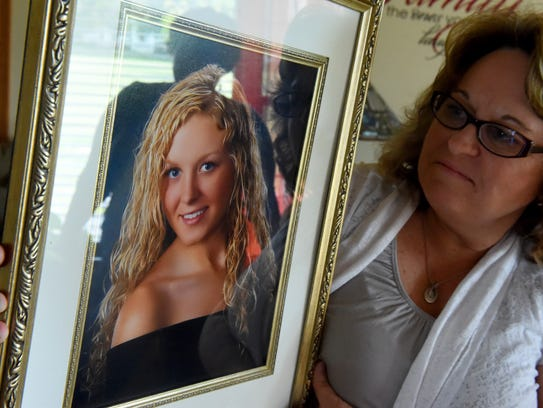 Kim Sours holds up a photo of her daughter, Keri Carter,