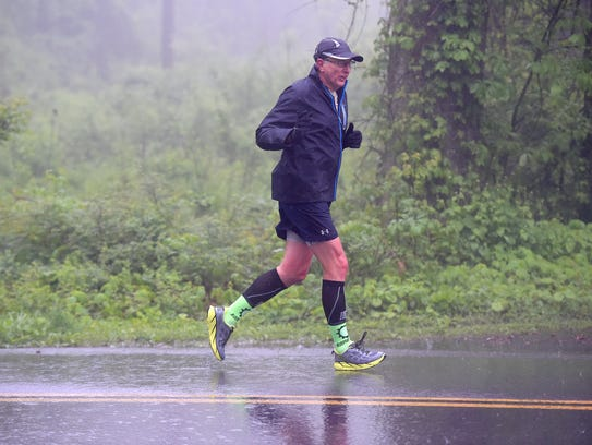 Ray Russell of Boone, N.C., runs through fog and rain