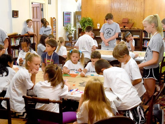 Camp participants make banners for the churches sponsoring