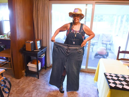 Linda Tabor holds up an old pair of jeans to show how