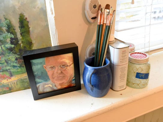 Brushes next to a small painting by artist Donna Cruce
