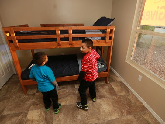 Brothers Angel and Osvaldo inspect their new bunk bed