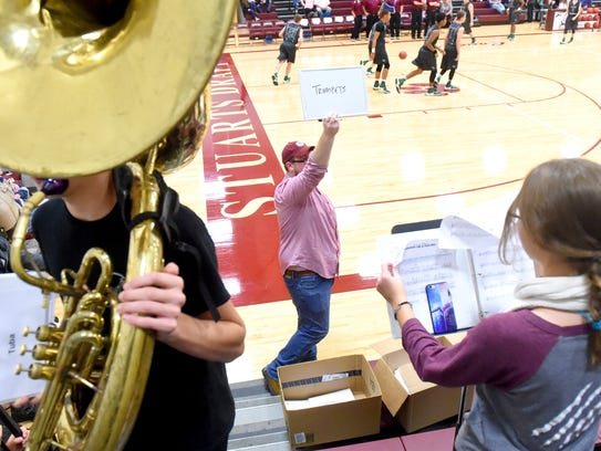 Band director Andrew Fauber holds up a sign letting
