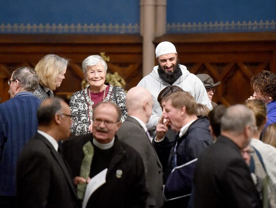 People of different faiths mingle and share in conversation
