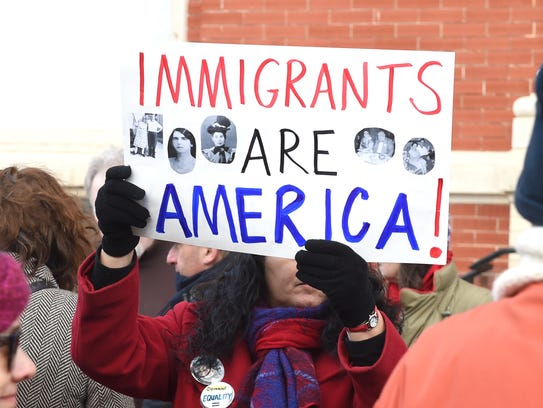 """A sign reading, """"Immigrants are America!,"""" is held"""