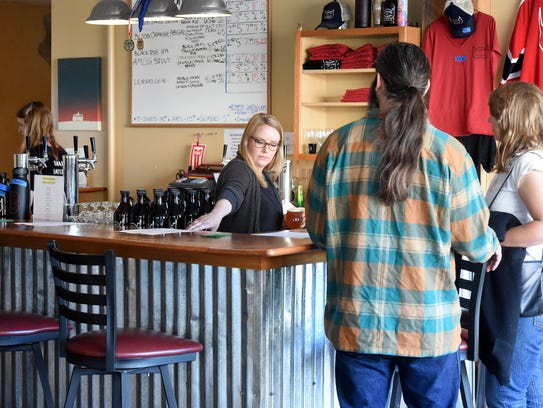 Taproom manager Amanda Mace Clark assists customers with their orders as she works behind the bar at Redbeard Brewing Co. in downtown Staunton on April 14, 2017.