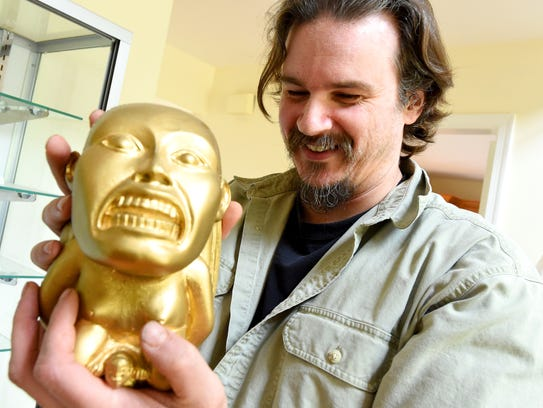 "Jarod Kearney holds a replica of the ""golden idol"""