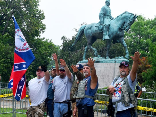 White nationalists offer a salute as they stand in