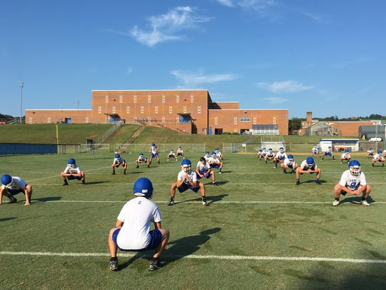 Fort Defiance players stretch before the first day