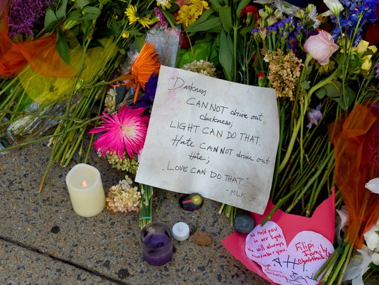 Flowers and words are left along 4th Street in remembrance