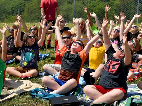 Fifth-graders raise their arms in the air and yell,