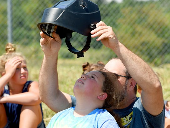 Fifth-graders use protective glasses as they watch