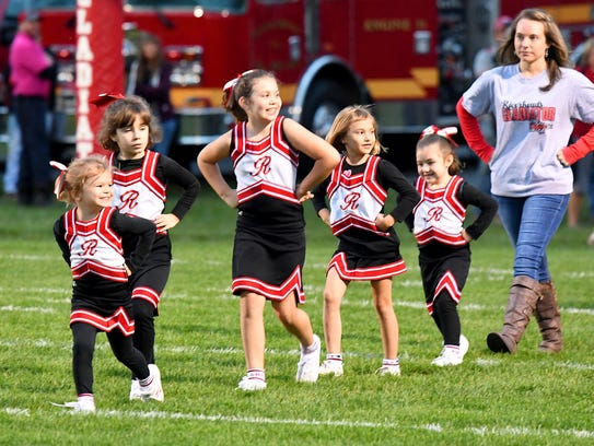 Young cheerleaders march onto the field together for