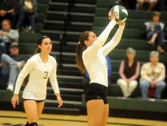Sam Kershner sets the ball while Hannah Johnson (3)