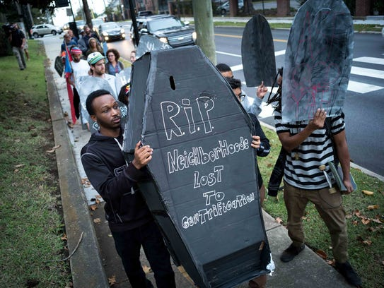 """Demonstrators march with signs during a """"funeral procession"""