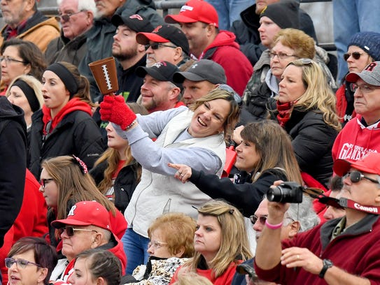 Bell in hand, a Riverheads' fan cheers while talking