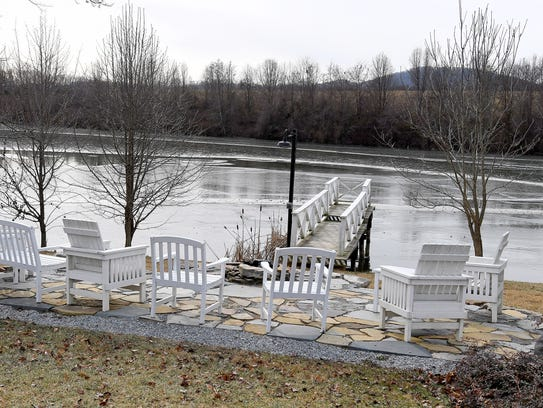Chairs overlook the lake while a dock leads out over