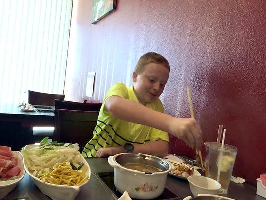 Daniel Groves, 11, enjoys an adventurous dinner at