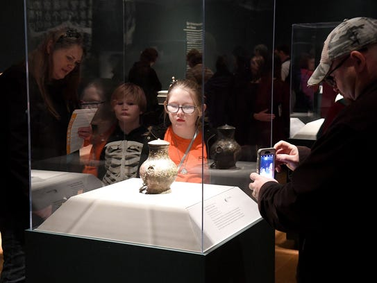 Museum visitors browse the various artifacts associated