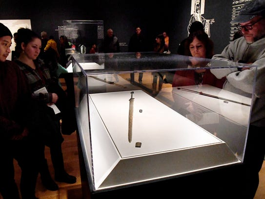 Museum visitors look at an ancient Chinese long sword