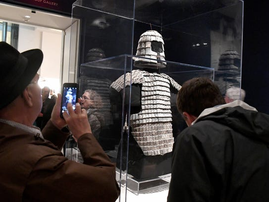"""Museum visitors look at """"Armor"""" Ñ one of the items"""